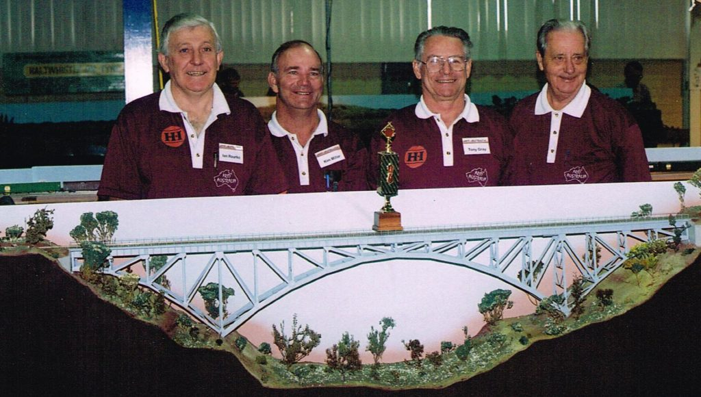 "Ian Rourke (left) with Kim Miller, Tony Gray and Len Hughes, part of the Arid Australia group and the AMRA trophy awarded to the best layout at the exhibition on Monday June 03 1996, the morning after the second World record train had been run. A very proud moment for Ian and the team involved with the Arid Australia ""project""."